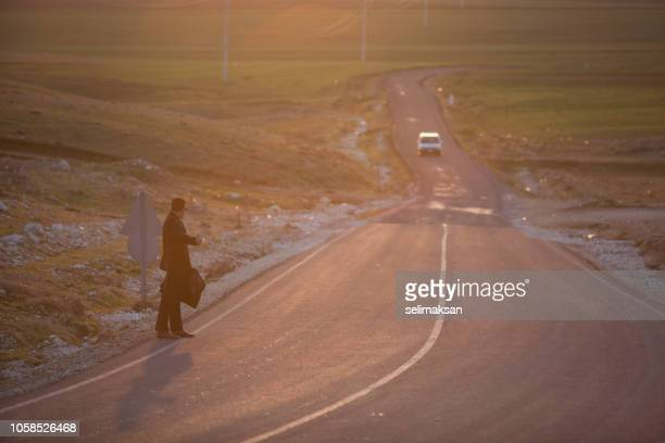 Businessman Hitchhikes  On Single lane Country Road