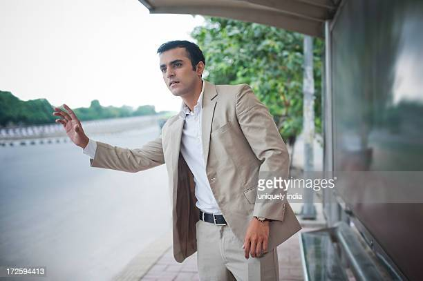 Businessman hitchhiking at bus stop