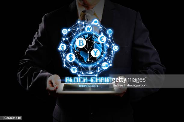 "Businessman hold the blockchain hologram on tablet, Business and Technology, Internet of thinks and network the concept of cryptocurrency, blockchain ""r""n""r""n"