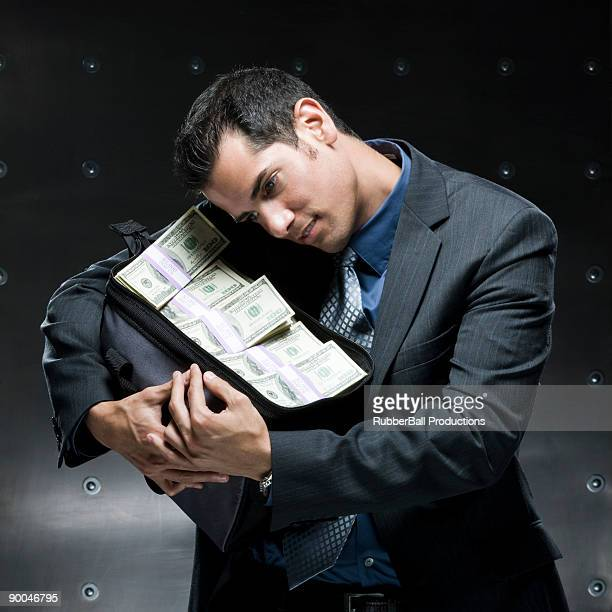 businessman holding a bag of money - money bag stock photos and pictures