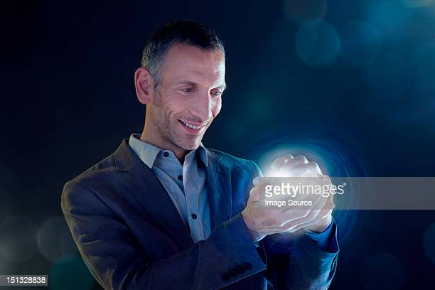 Businessman holding a ball of light