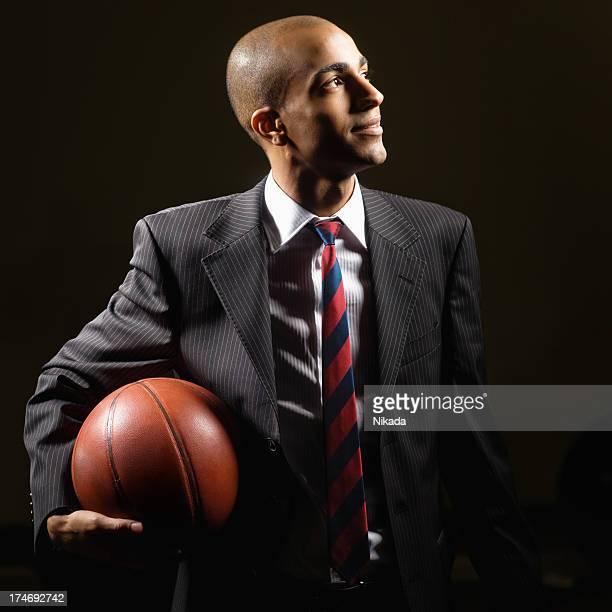 businessman holding a basket ball