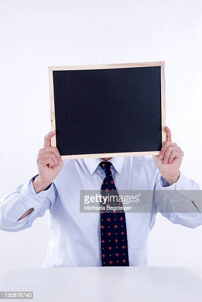 Businessman holding a blank blackboard