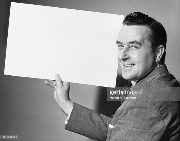 Businessman Holding A Blank Poster Board