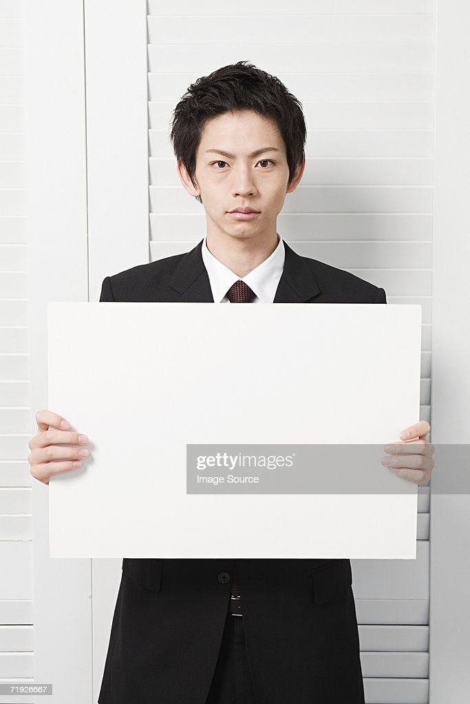 Businessman holding a blank sign : Stock Photo