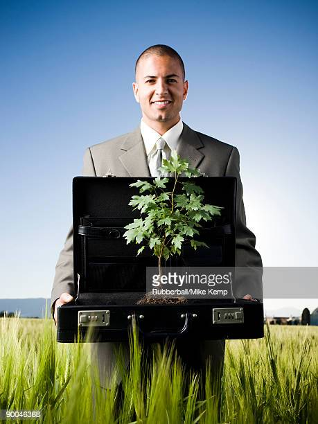 businessman holding a briefcase with a tree in it