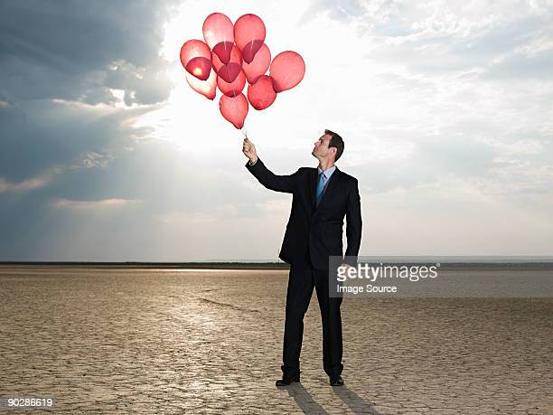 Businessman holding a bunch of red balloons