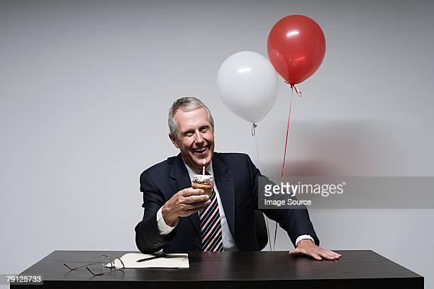 Un hombre de negocios sosteniendo un pastel