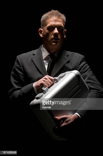un hombre de negocios sosteniendo un caso contra un fondo negro. - top fotografías e imágenes de stock