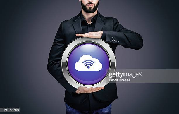 Businessman holding a circle containing the Cloud pictogram