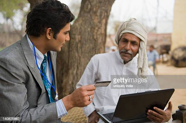 Businessman holding a credit card sitting with a farmer holding a laptop, Hasanpur, Haryana, India