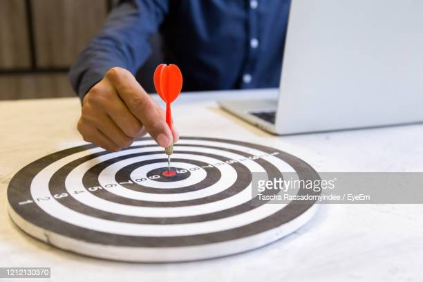 businessman holding a darts aiming at the target center,business growth success concept. - achievement stock pictures, royalty-free photos & images