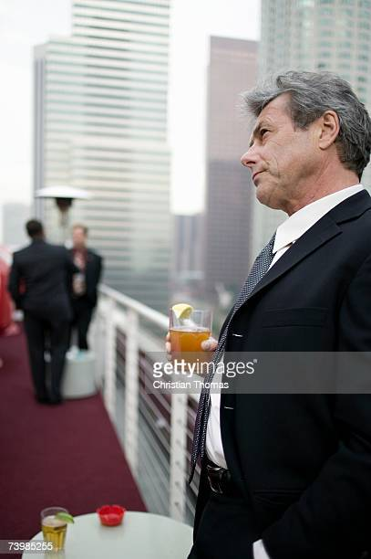 Businessman holding a drink at a roof top bar