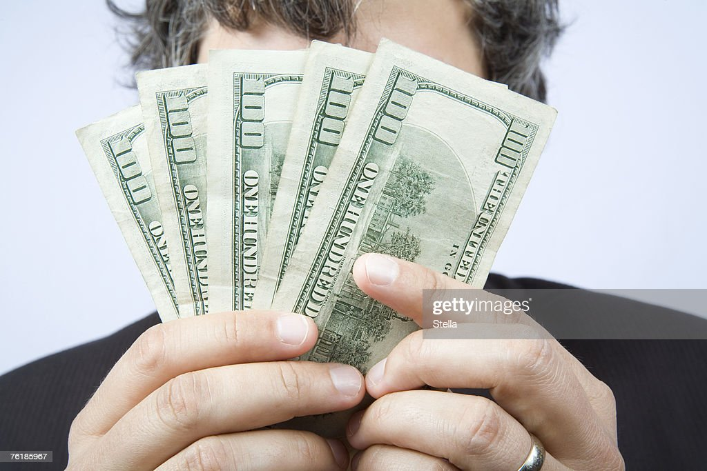A businessman holding a fan of hundred dollar bills in front of his face : Stock Photo
