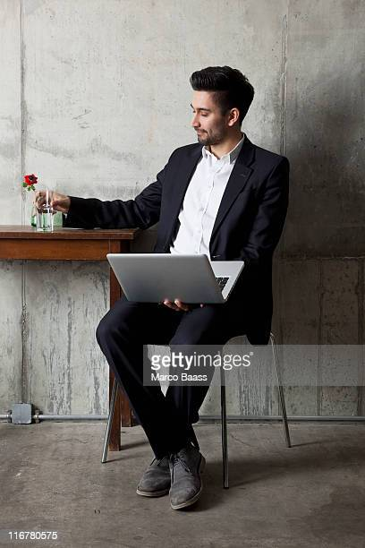 A businessman holding a glass of water and a laptop