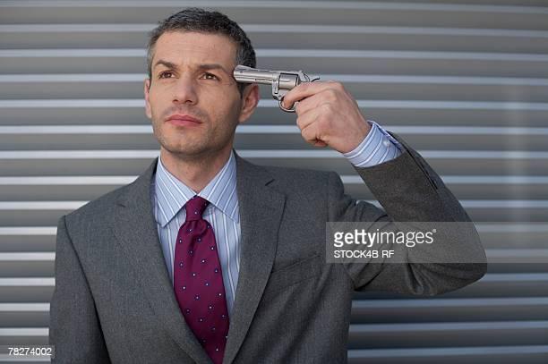 Businessman holding a gun to head