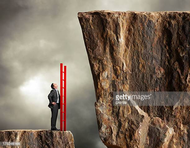 Businessman holding a ladder looks up towards higher level