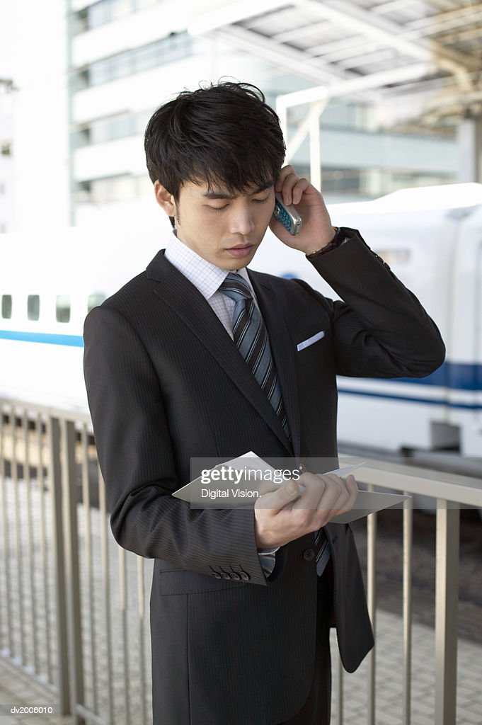 Businessman Holding a Mobile Phone and Looking at a Diary : Stock Photo