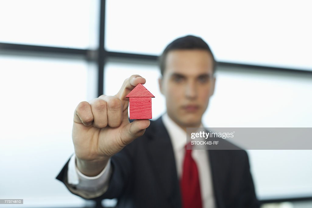 Businessman holding a model house between fingers : Photo