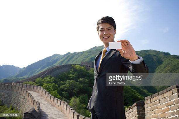 Businessman holding a name card on the Great Wall