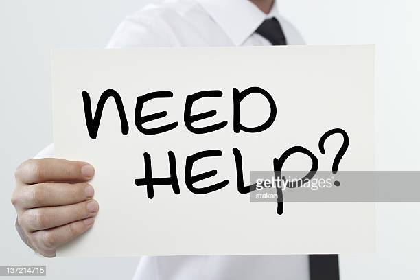 A businessman holding a need help sign