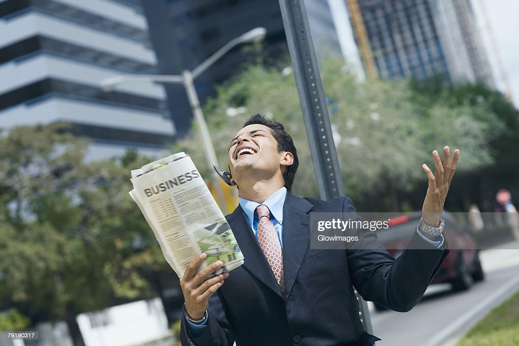 Businessman holding a newspaper and smiling : Stock Photo
