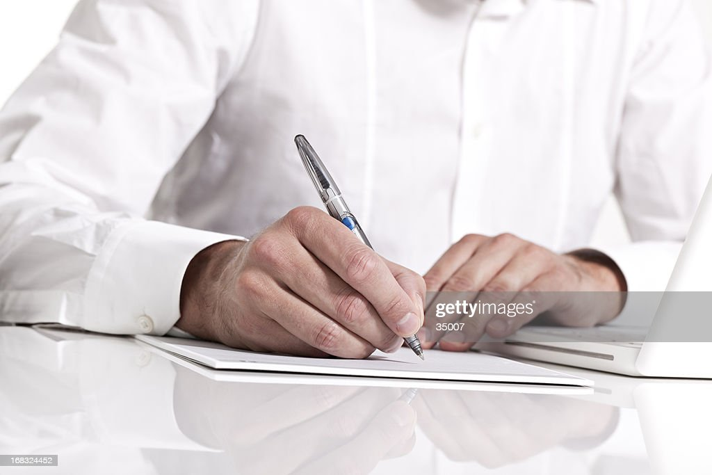 Businessman holding a pen & taking notes on paper : Stock Photo
