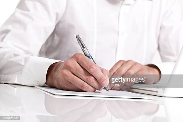 businessman holding a pen & taking notes on paper - petition stock photos and pictures