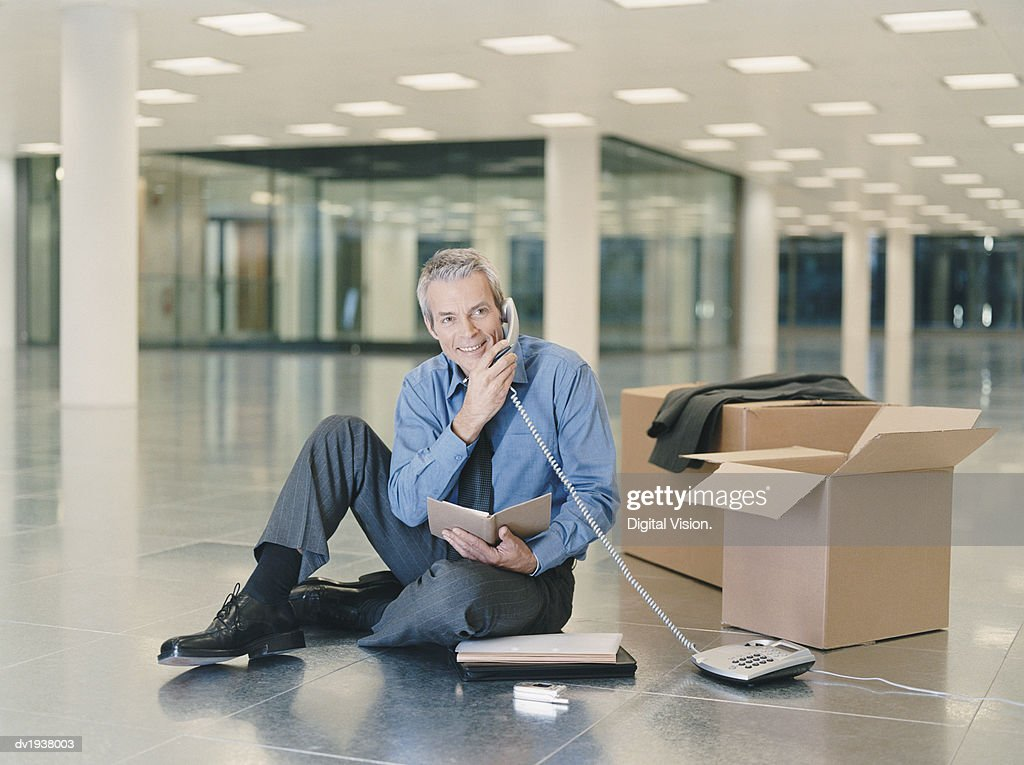 Businessman Holding a Phone Receiver Sitting in an Empty Office : Stock Photo