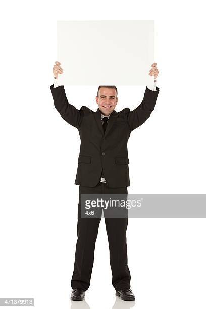 Businessman holding a placard