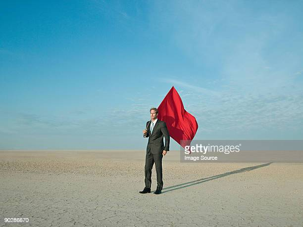 businessman holding a red flag in a desert - flag stock pictures, royalty-free photos & images