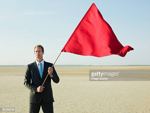 Businessman holding a red flag