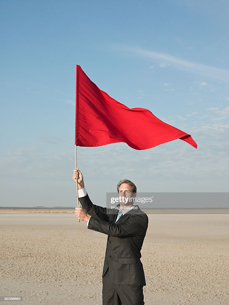 Businessman holding a red flag : Stock Photo