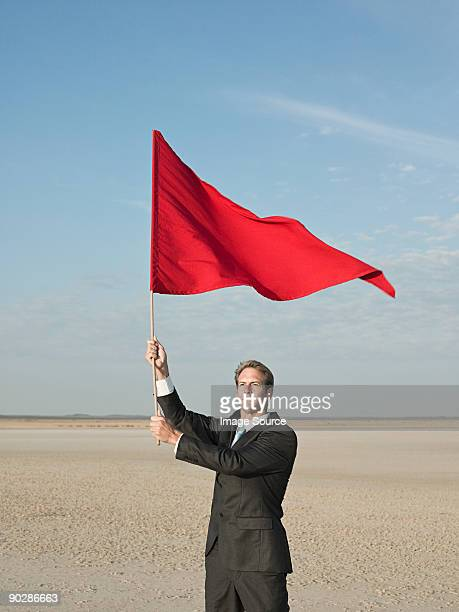 businessman holding a red flag - flag stock pictures, royalty-free photos & images