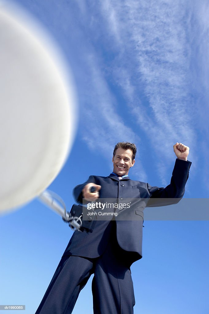 Businessman Holding a Satellite Dish With His Fist in the Air : Stock Photo