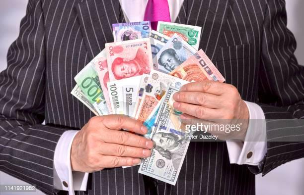 businessman holding a selection of banknotes - devisenkurs stock-fotos und bilder