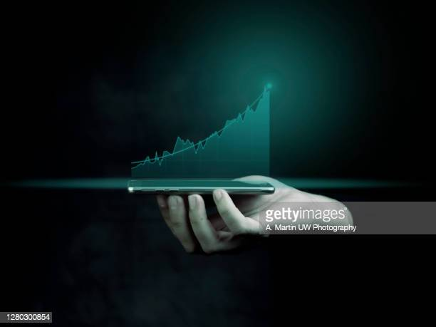 businessman holding a smart phone and showing holographic graphs and stock market statistics gain profits. concept of growth planning and business strategy. display of good economy form digital screen. - finanza ed economia foto e immagini stock