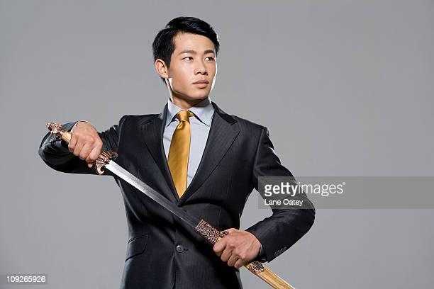 Businessman holding a sword