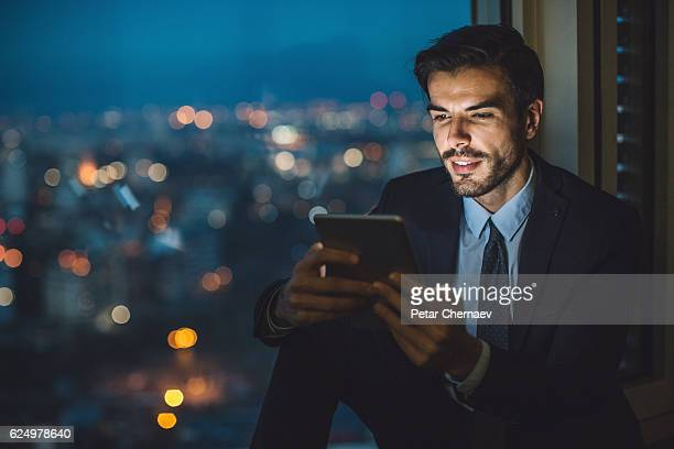 Businessman holding a tablet at night