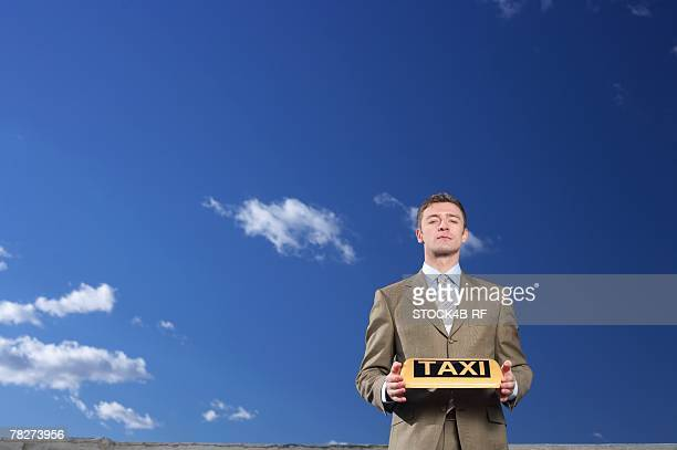 Businessman holding a taxi sign
