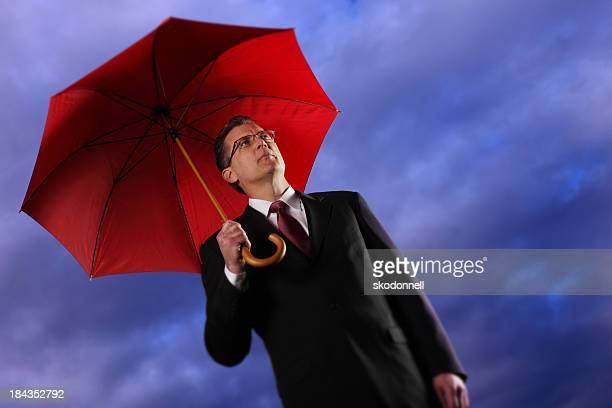 businessman holding a umbrella - bear market stock pictures, royalty-free photos & images