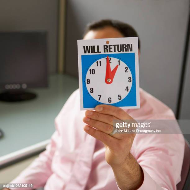 Businessman holding a will return sign in front of his face