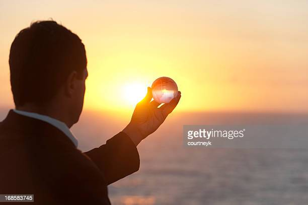 Businessman holding a world globe at dawn