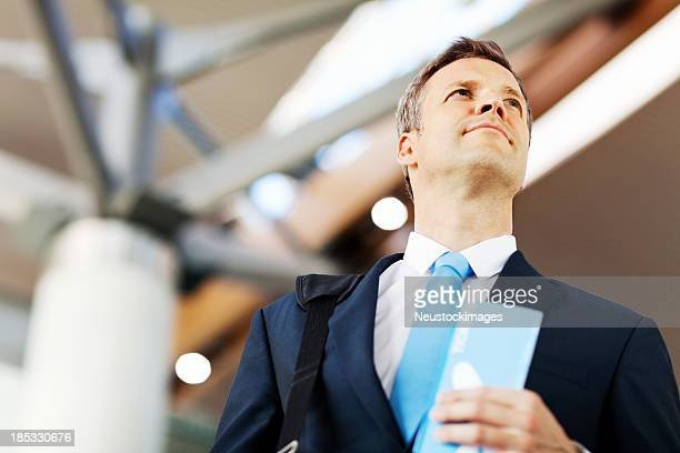 Businessman Holding Airline Tickets At Airport