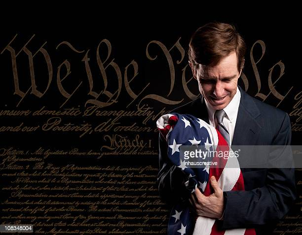 Businessman holding American Flag Bill of Rights in the Background