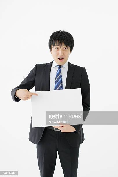 Businessman holding and pointing at white board, studio shot