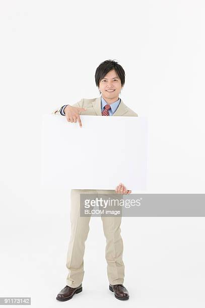 Businessman holding and pointing at whiteboard