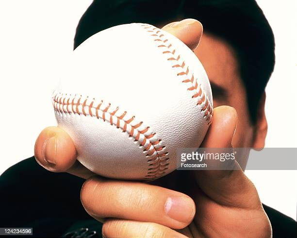 Businessman holding and raising a baseball, High Angle View, Close Up