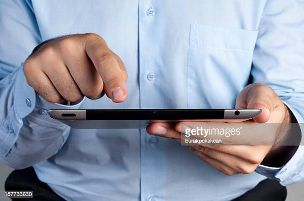 Businessman holding Apple iPad and finger tapping on the screen