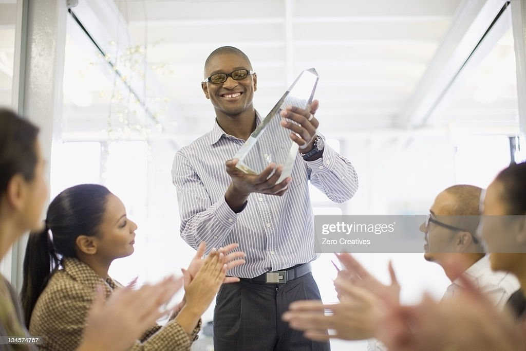 Businessman holding award in meeting : Stock Photo